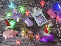 Decorative seasonal composition of Christmas toy piglets in Santa`s red hats, festive illumination. Candles, boxes with balls, lanterns on a wooden table, pink royalty free stock image