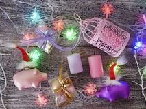 Decorative seasonal composition of Christmas toy piglets in Santa`s red hats, festive illumination. Candles, boxes with balls, lanterns on a wooden table, pink stock images