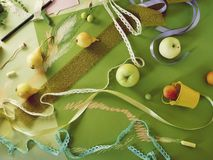 Decorative seasonal composition of fruit, decor, greenery on green tinted paper royalty free stock images