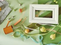 Decorative seasonal composition of fruits, decor, greens and a white frame on green toned paper stock images