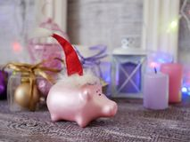 Decorative seasonal composition of a New Year`s pig toy in a red Santa hat, festive illumination, candles. Boxes with balls, lanterns on a wooden table, pink stock photography