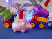 Decorative seasonal composition of toy cars, Christmas toys, pigs in red felt Santa hats, Christmas decor, bright lighting, illumi stock image