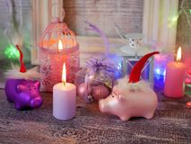 Decorative seasonal composition of toy New Year piglets in red Santa hats, festive illumination, lit candles. Boxes with balls, lanterns on a wooden table stock photos