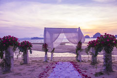 Decorative setting for wedding ceremony on the beach. With sunset as a background Stock Photos