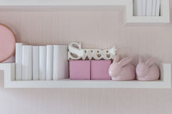 Decorative shelf on pink wall with rabbits ceramic and word Stock Photo