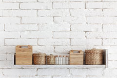 Decorative shelf. On white brick wall with vintage bottles and wicker jars on it royalty free stock images