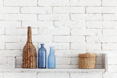 Decorative shelf. On white brick wall with vintage bottles and wicker jars on it royalty free stock image