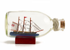 Decorative ship in glass bottle. On wooden support isolated on white Royalty Free Stock Photo