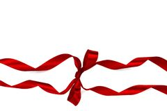 Decorative silk red ribbon with a bow on isolated white background. Cut out. royalty free stock photo