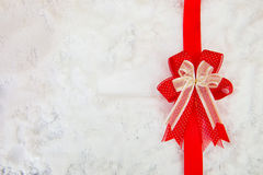 Decorative simple gold ribbon and bow on a background of winter Stock Image