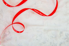Decorative simple gold ribbon and bow on a background of winter Royalty Free Stock Photos