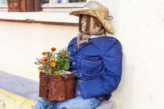Decorative sitting scarecrow  with flowers Stock Photography