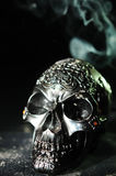 Decorative Skull With Smoke Trail. Dark and moody still life image of an embossed ornamental  skull, with a smoke trail in the background Stock Photos