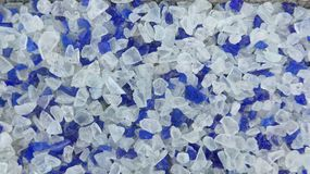 Decorative small blue and white shards of glass, close-up. Background stock photo