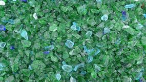Decorative small green and turquoise shards of glass, close-up. Decorative small green and turquoise shards of glass as a background royalty free stock image