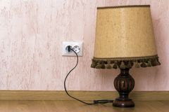 Decorative small wooden lamp with cloth top plugged in wall sock Royalty Free Stock Images
