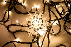 Decorative snow flake lying on christmas lights. Closeup photo of decorative snow flake lying on christmas lights Royalty Free Stock Photography