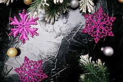 Decorative snowflake white and pink on black background. Christmas greeting card. Copy space. Top view. Stock Photography