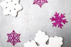 Decorative snowflake white and pink on grey background. Christmas greeting card. Copy space. Top view. Stock Photos