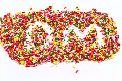 Decorative sprinkles sugar in alphabet shape as DM  on  white ba Royalty Free Stock Image