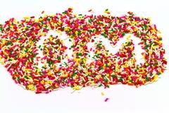 Decorative sprinkles sugar in alphabet shape as DM  on  white ba Royalty Free Stock Image