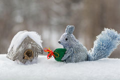 Decorative squirrel with a bag of gifts and a small house for birds in the snow, Royalty Free Stock Images