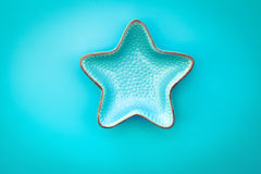 Decorative star-shaped bowl over blue background Stock Photos