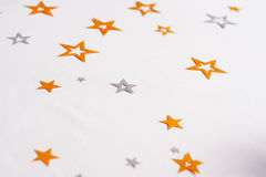 Decorative star on a white tablecloth. White tablecloth decorated with stars of gold or silver Royalty Free Stock Photos