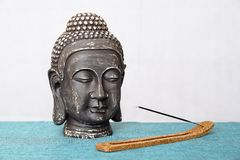 A decorative statue of Buddha, Buddha on the background of incense, Siddhartha Gautama has reached enlightenment. Symbol. Decorative Buddha statue, Buddha on the stock photography