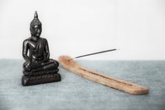 A decorative statue of Buddha, Buddha on the background of incense, Siddhartha Gautama has reached enlightenment. Symbol. Decorative Buddha statue, Buddha on the stock photos