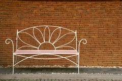 Decorative Steel Bench with Brick Wall Background. Decorative Steel Bench with Red Brick Wall Background stock images