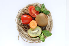 Decorative stillife with vegetables. Stillife of tomato, kiwi, piece of carrot in the Wicker basket royalty free stock image
