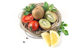 Decorative stillife with vegetables. Stillife of tomato, kiwi, piece of carrot in the Wicker basket royalty free stock photography