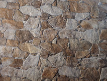 Decorative stone wall. Of gray-brown stone of different sizes Stock Image