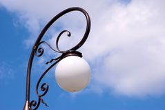 Decorative street lamp. Decorative metal street lamp with blue sky and cloudscape background Stock Photo