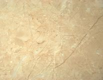 Decorative surface, beige marble with white veins. A close-up shot. royalty free stock photo