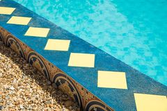 Pool edge. Decorative swimming pool edge with vintage tiles on wall and blue paint color concrete on top Stock Photos