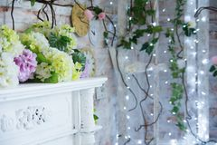 Decorative table with artificial flowers and a background of burning garlands royalty free stock photos