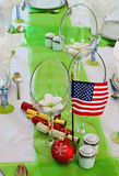 Decorative table settings. Place settings and decorative table centerpieces including firecrackers, US flag and flower vases Stock Photo
