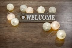 Decorative text welcome with heart and lights on the wooden table. Decorative wooden text with heart and multicolored lights on the wooden table Stock Images