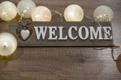 Decorative text welcome with heart and lights on the wooden table. Decorative wooden text with heart and multicolored lights on the wooden table Royalty Free Stock Photos