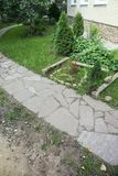 Path paved with a natural stone in a autumn garden. the inner yard is paved with decorative grey natural stone. Stock Photos