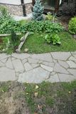 Path paved with a natural stone in a autumn garden. the inner yard is paved with decorative grey natural stone. Royalty Free Stock Photo