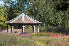Decorative tiled gazebo structure in ornamental flower garden Stock Photography