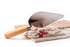 Decorative tiles. Tiles squares on the ground, cross and trowel on a white background Stock Photo