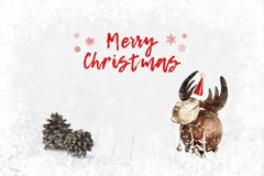 Decorative toy deer and pine cones on bokeh winter wooden background. Light soft Christmas background. royalty free stock photo