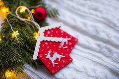 Decorative toy houses with deer near fir wreath with red Christmas balls and coiled with glowing garland with warm light on white. Knitted plaid. New Year home royalty free stock image