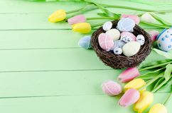 Decorative toys eggs in the nest. Decorative eggs toys in the nest and tulips for Easter on thelight  green background. Copy space, top view concept of Easter Royalty Free Stock Images