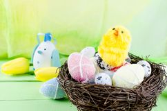 Decorative toys eggs in the nest. Decorative eggs toys in the nest and tulips for Easter on thelight  green background. Copy space, top view concept of Easter Royalty Free Stock Photo
