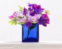 Decorative traditional blue bottle. With fake flowers in it at Santorini island, Greece Stock Image